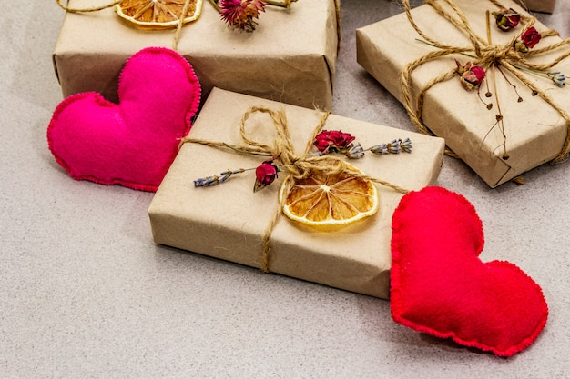 廃棄物ゼロギフトコンセプト。バレンタインデーまたは誕生日の環境に優しいパッケージ。さまざまな有機装飾が施されたクラフト紙のお祝いボックス。