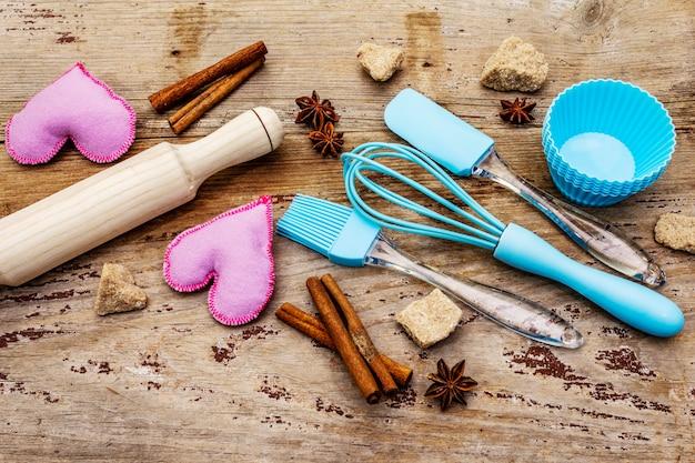 カップケーキ、スパイス、砂糖、泡立て器、ヘラ、麺棒、フェルトハート用のシリコン型。古い木の板