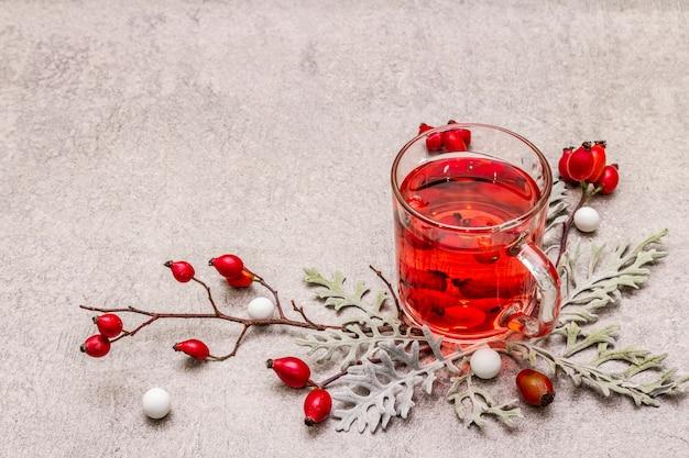 Горячий чай из шиповника. зимний напиток для хорошего настроения со свежими ягодами, листьями и конфетами.