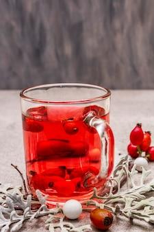 ホットドッグローズティー。新鮮なベリー、葉、キャンディーで気分を良くする冬の飲み物。