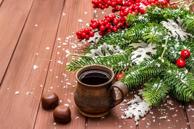クリスマスホットコーヒー。新年のモミの木、犬のバラ、新鮮な葉、チョコレート菓子、人工雪。