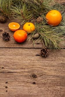 木製のテーブルの上の精神のクリスマス。新鮮なオレンジ、みかん、松の枝、コーン。自然の装飾、ヴィンテージの木製ボード