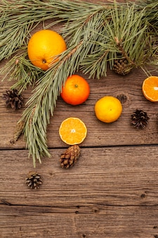 Дух рождества на деревянный стол. свежие апельсины, мандарины, сосновые ветки и шишки. природные украшения, старинные деревянные доски