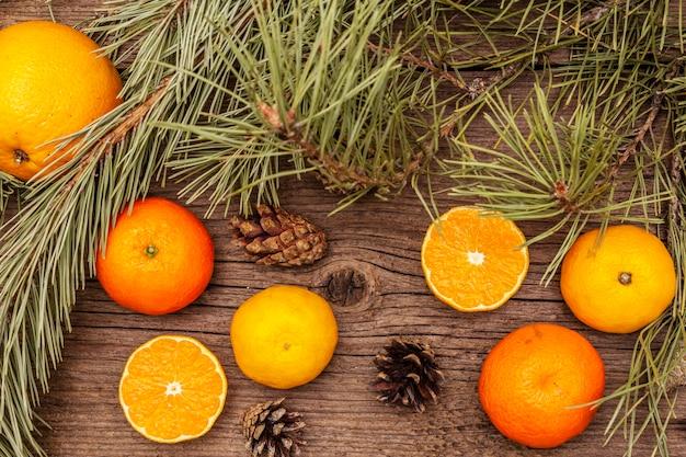Свежие апельсины, мандарины, сосновые ветки и шишки. природные украшения, старинные деревянные доски