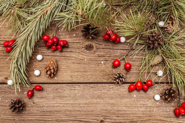 木製のテーブルの上の精神のクリスマス。新鮮な犬のバラの果実、ボールキャンディー、松の枝とコーン、人工雪。自然の装飾、ヴィンテージの木製ボード