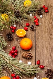 木製のテーブルの上の精神のクリスマス。新鮮なマンダリン、ドッグローズベリー、キャンディー、松の枝とコーン、人工雪