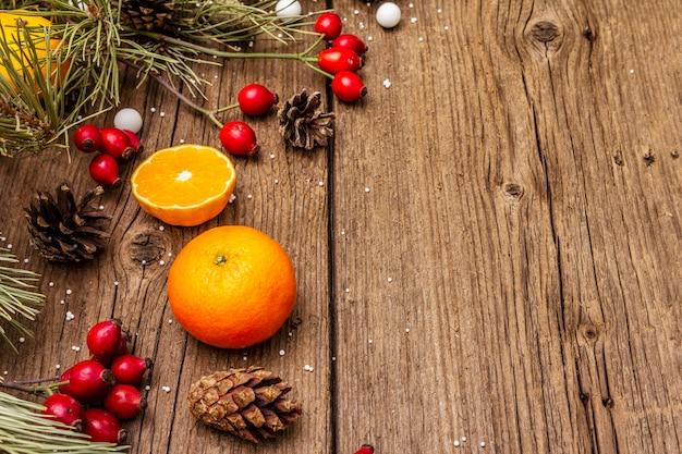 Дух рождества на деревянный стол. свежие мандарины, шиповник, конфеты, сосновые ветки и шишки, искусственный снег