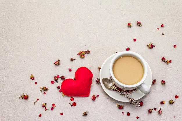Чашка кофе, бутоны роз и лепестки и красное войлочное сердце