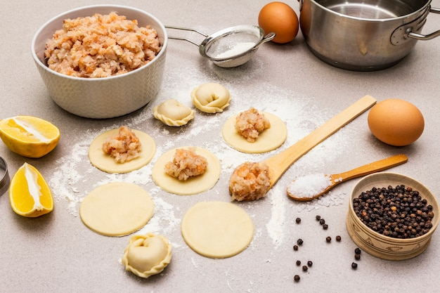Рыбные пельмени. ингредиенты для домашней кухни. свежее тесто, рыба, специи, кухонное оборудование. камень бетонный фон