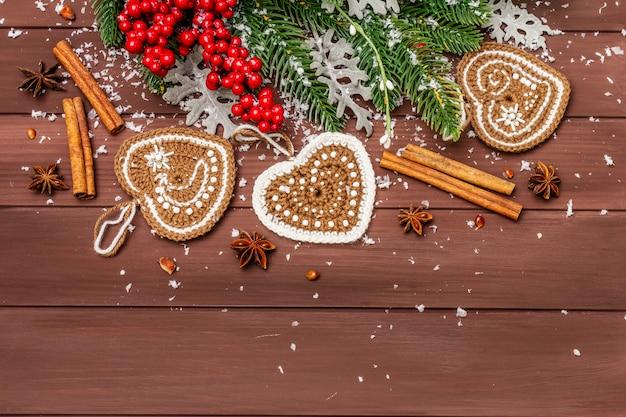 クリスマスの背景。新年のモミの木、犬のバラ、新鮮な葉、かぎ針編みのジンジャークッキーの心、スパイス、人工雪。