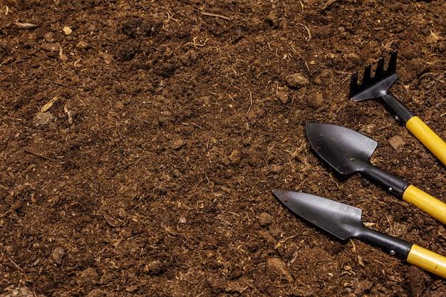 Садовые инструменты на фоне почвы. концепция ухода за растениями. лопаты и грабли