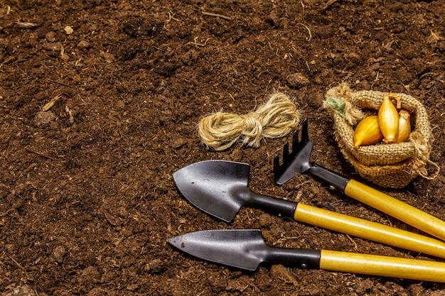 Садовые инструменты на фоне почвы. концепция ухода за растениями. лопатки и грабли, нитки, лук