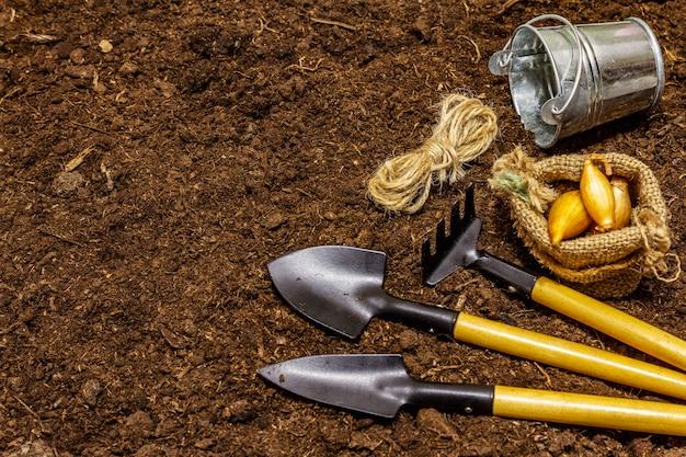 Садовые инструменты на фоне почвы. концепция ухода за растениями. лопатки и грабли, ведро, нить, лук