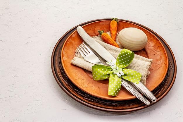 Сервировка стола пасхи на текстурированной белой предпосылке замазки. весенний праздник шаблон карты. столовые приборы, винтажная салфетка, яйцо, морковь, зайчик