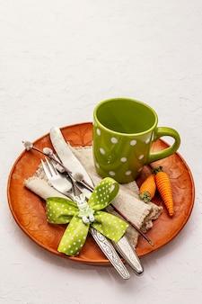Сервировка стола пасхи на текстурированной белой предпосылке замазки. весенний праздник шаблон карты. столовые приборы, чашка, винтажная салфетка, яйцо, морковь, зайчик