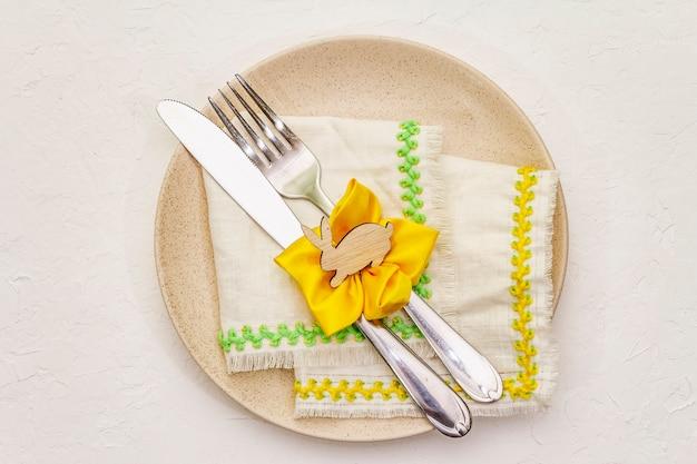Сервировка стола пасхи на текстурированной белой предпосылке замазки. весенний праздник шаблон карты. столовые приборы, винтажная салфетка, кролик, цветок