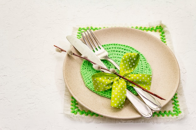 Сервировка стола пасхи на текстурированной белой предпосылке замазки. весенний праздник шаблон карты. столовые приборы, вышитая салфетка, бантик, ивовые пломбы