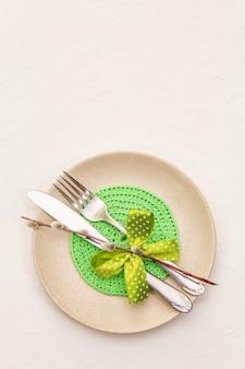 Сервировка стола пасхи на текстурированной белой предпосылке замазки. весенний праздник шаблон карты. столовые приборы, вязаная салфетка, бантик, ивы