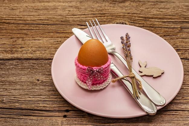 ヴィンテージの木製ボードの背景にイースターテーブルの設定。春のホリデーカードテンプレート。カトラリー、卵、ラベンダー、バニー、ニットスタンド