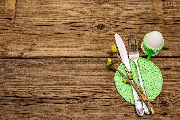 Сервировка стола пасхи на античной деревянной предпосылке. весенний праздник шаблон карты. столовые приборы, вязаная салфетка, яйцо, веточки сирени