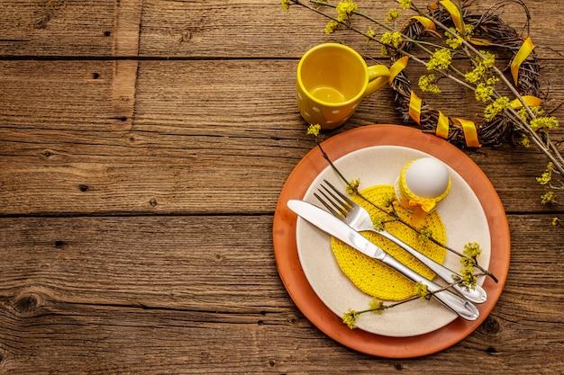 Сервировка стола пасхи на старой деревянной предпосылке. весенний праздник шаблон карты. столовые приборы, вязаная салфетка, яйцо, цветущие веточки кизила, чашка, венок