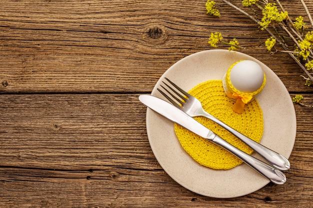 Сервировка стола пасхи на старой деревянной предпосылке. весенний праздник шаблон карты. столовые приборы, вязаная салфетка, яйцо, цветущие веточки кизила