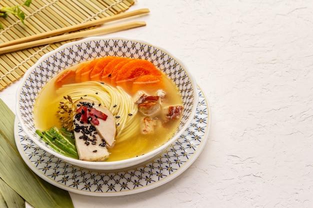 スモークチキンと野菜の韓国ラーメンスープ。健康的な食事のための春のスパイシーな料理