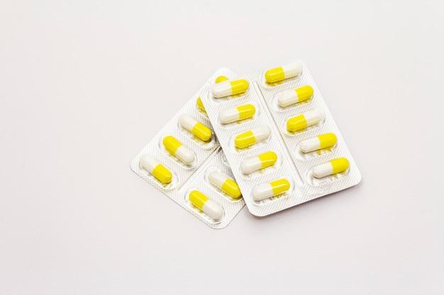 Фармацевтические таблетки, желтые белые капсулы в блистерной упаковке на белом фоне