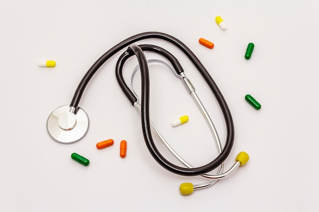 Медицинский стетоскоп и таблетки на белом фоне