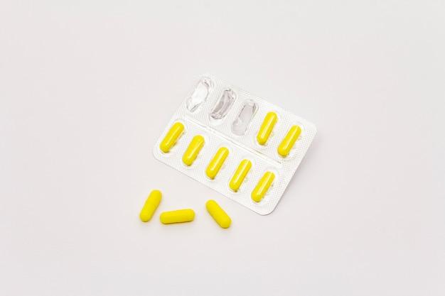 Фармацевтические таблетки, желтые капсулы в блистерной упаковке на белом фоне