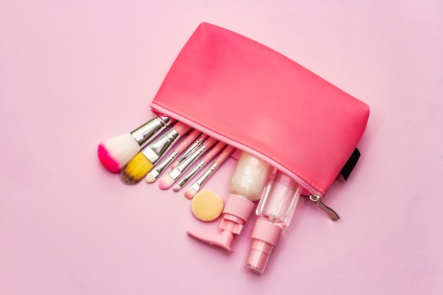 Макияж косметический набор в сумке на розовом фоне