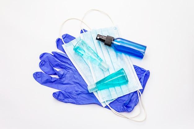 Маска, перчатки, дезинфицирующее средство на белом фоне