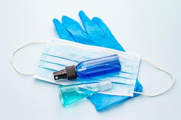 Маска, перчатки, дезинфицирующее средство на синем фоне