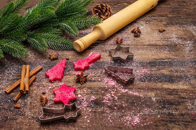 レッドジンジャークッキーを調理します。伝統的なクリスマスのペストリー。お祭りの料理の背景。モミの木、スパイス、クッキーカッター、生生地、麺棒、木の板