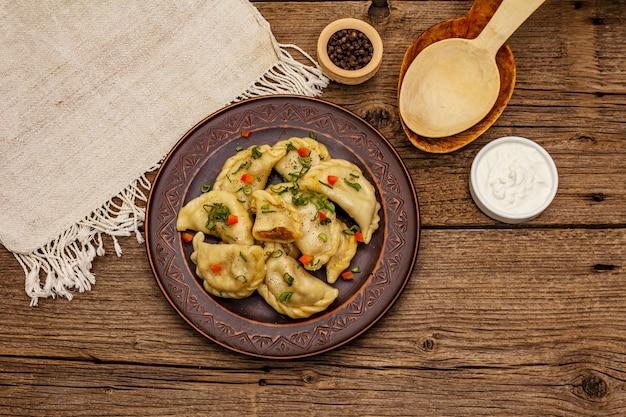 Пельмени фаршированные тушеной капустой и сметаной. традиционное украинское блюдо вареники