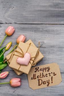 幸せな母の日のグリーティングカード。優しいピンクのチューリップ、手作りのフェルトハート