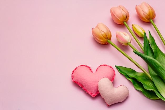Букет романтических тюльпанов на розовый стол с сердечками. валентина концепция