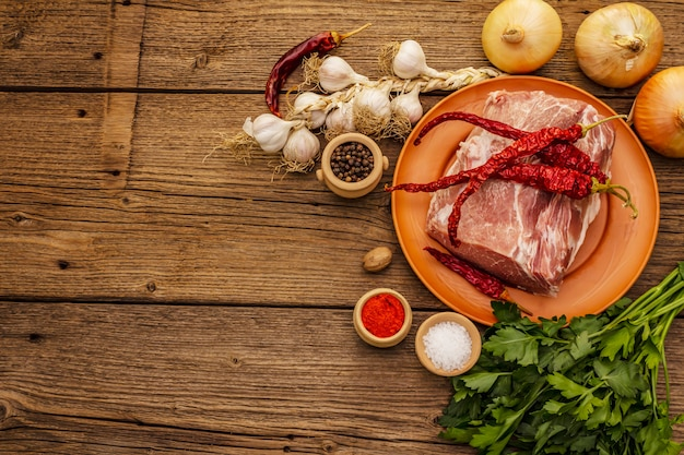Сырое свиное мясо. свежая корейка, специи, ароматные овощи и петрушка