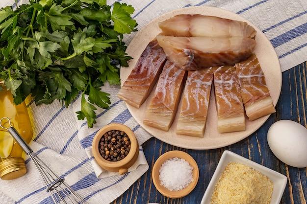 サイゼとフライの材料の生の切り身。プレート、スパイス、卵、油、パン粉、パセリの新鮮なスライス