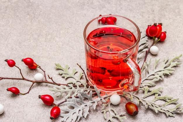 ホットドッグローズティー。新鮮なベリー、葉、キャンディーを使った気分の良い冬の飲み物。