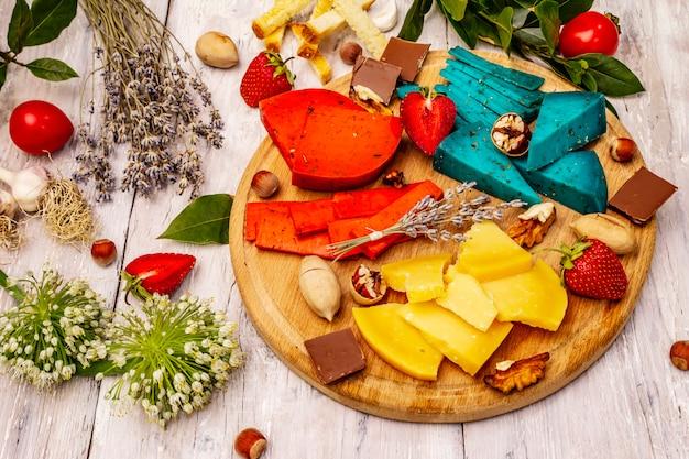 ホワイトボードの背景にマルチカラーのハードダッチチーズの盛り合わせ