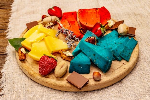 木の板の背景に盛り合わせマルチカラーハードオランダチーズ