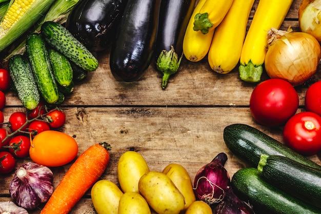 Урожай разнообразных спелых овощей. свежие огурцы, помидоры, баклажаны, цуккини, лук, чеснок, картофель, морковь. старые деревянные доски фон, место для текста, вид сверху