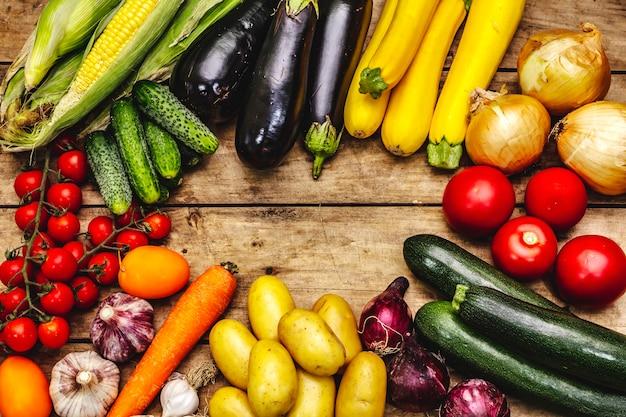 Урожай разнообразных спелых овощей. свежие огурцы, помидоры, баклажаны, цуккини, лук, чеснок, картофель, морковь. старые деревянные доски фон, место для текста, крупным планом