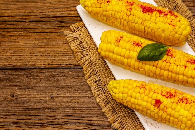 セラミックプレートにゆでたトウモロコシの穂軸。海塩、香りパプリカ、フレッシュバジルの葉