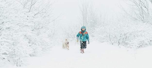 冬に歩いている犬を持つ少年