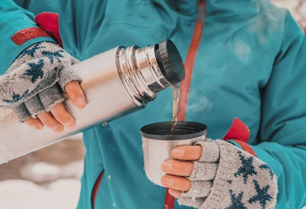 魔法瓶からお茶を注ぐ観光客