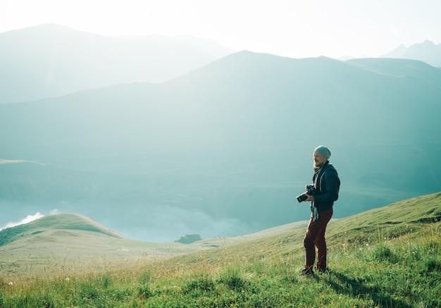 Фотограф человек гуляет в горах.