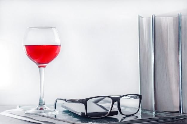 Концепция интернет-образования, домашнего обучения. на столе стакан красного вина, ряд книг, стаканы, смартфон и рабочая тетрадь.