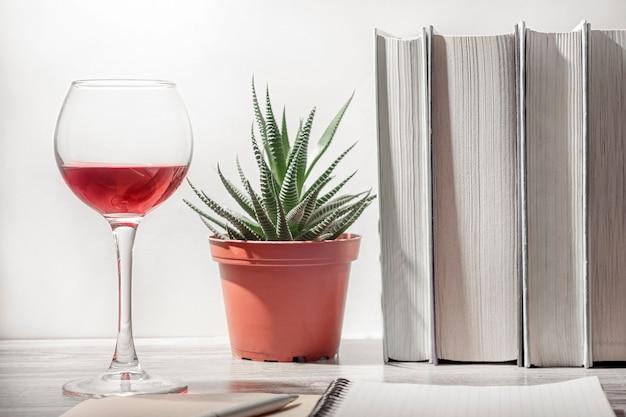 Концепция интернет-образования, домашнего обучения. на столе стакан красного вина, ряд книг, комнатное растение, блокнот и ручка.